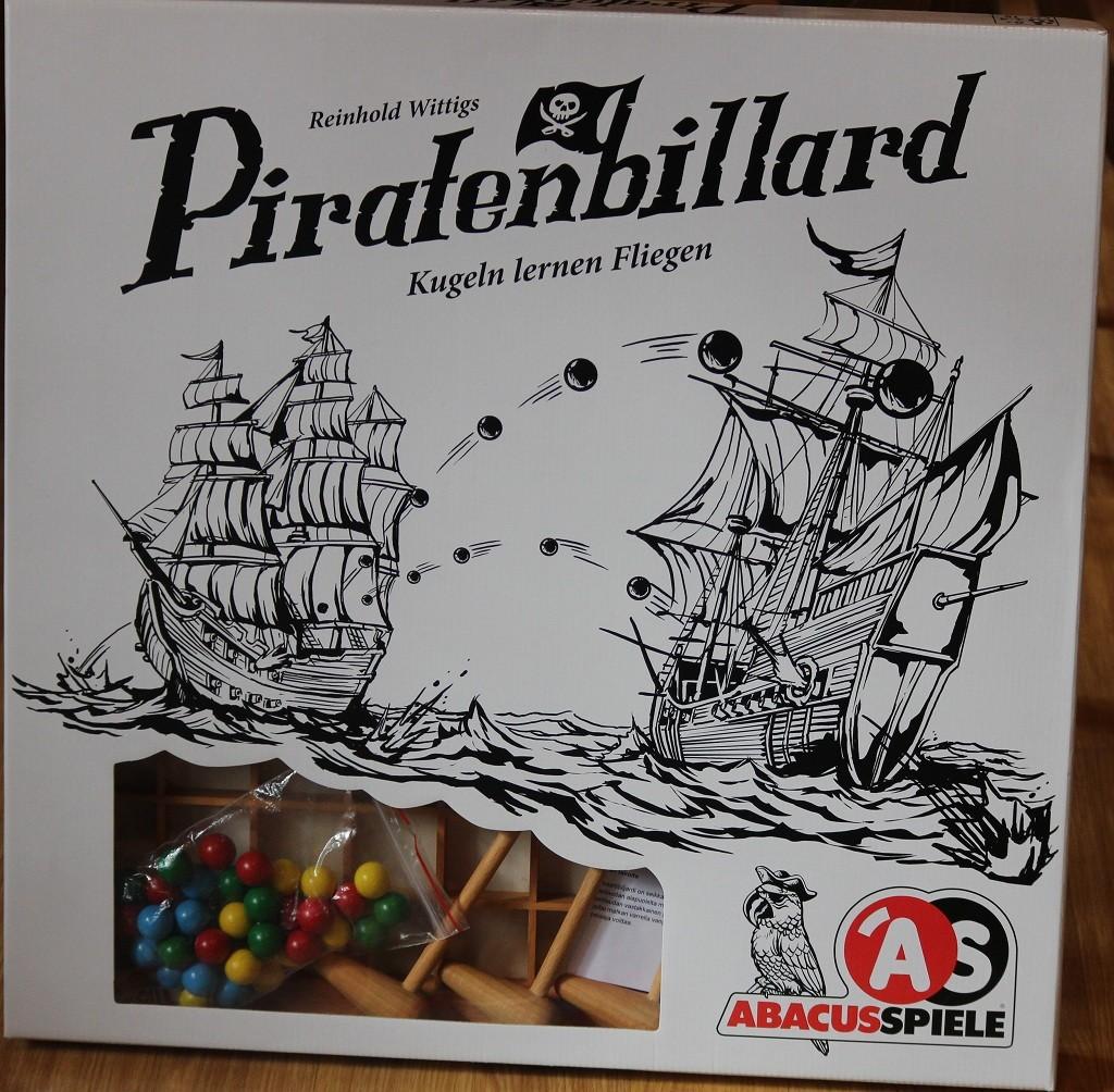 """Piratenbillard pelilaatikon kansi, jonka """"kurkistusluukusta"""" näkyy mailat ja puupalloja."""