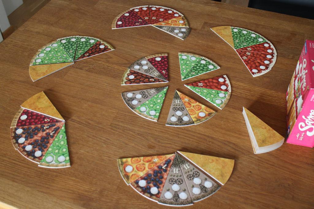 Neljäs kierros menossa. Kierroksen kakku on jaettu, nyt pelaajat pääsevät valitsemaan osansa. Ympärillä pelaajien aiempien kierrosten saaliit.