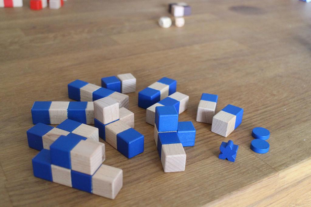 Sinisen pelaajan komponentit: 12 rakennuspalaa, kiipeilijä ja kaksi kertakäyttöistä nappia hädän hetkellä käytettäväksi.