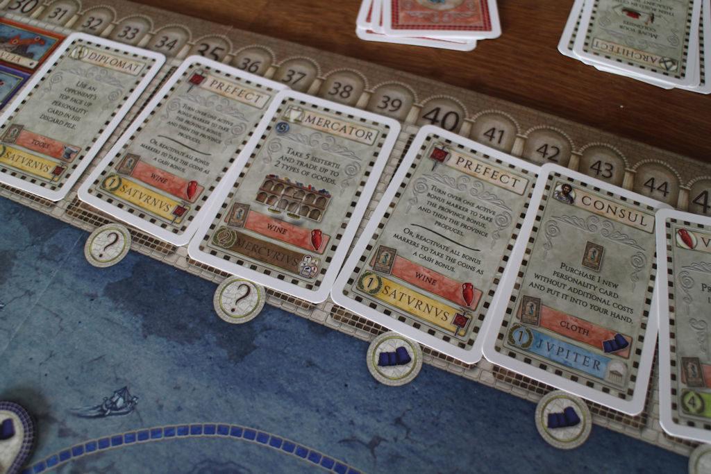 Korttimarkkinat. Hinta näkyy korteissa punaisella + lisähinta on painettu pelilautaan.