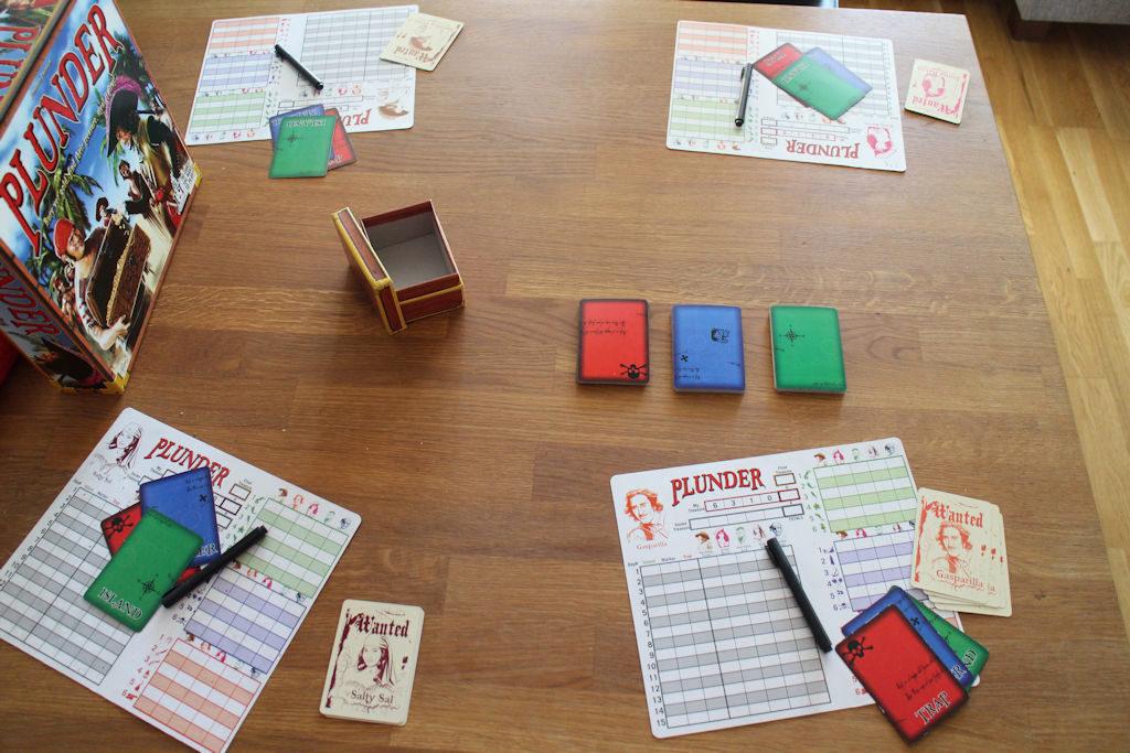 Alkuvalmistelut tehty. Pelaajille jaettuna muistiinpanolaput, tussit, oman aarteen koordinaatit ja pelaajien verran ratkaisukortteja käytettäväksi. Keskellä koordinaattikortit odottavat käyttämistään.