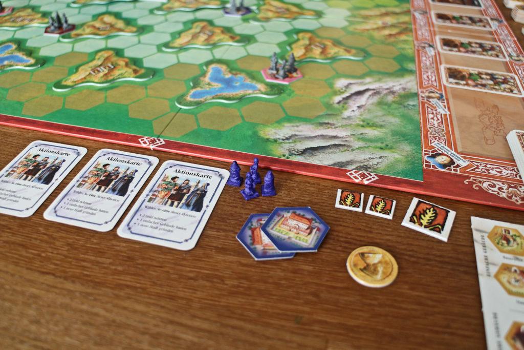 Pelaajien ruoantuotantoa seurataan viljanattereilla. Sininen pelaaja tuottaa 7 viljaa, joilla ruokkii yhtä monta kansalaista. Vasemmalla pelaajan vakiokortit, joilla on kolme eri funktiota.