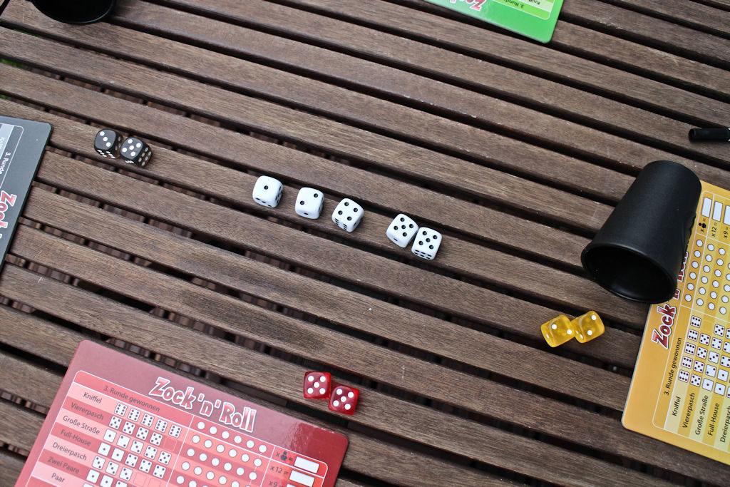Kolme pelaajaa ratkaisemassa voittajaa: keltaisella täyskäsi, mustalla suora, punaisella neloset.
