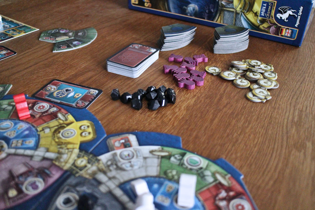 Pelin komponentteja: mustia timantteja, violetteja octopodeja, keltaisia aikamerkkejä, teknologiakortteja ja laboratoriolaattoja.