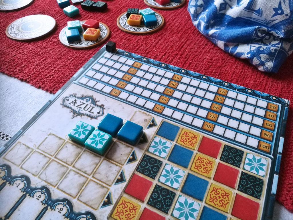 Pelaajalauta ja viisi riviä, johoon kierroksen aikana otetut kaakelit pitää varastoida.