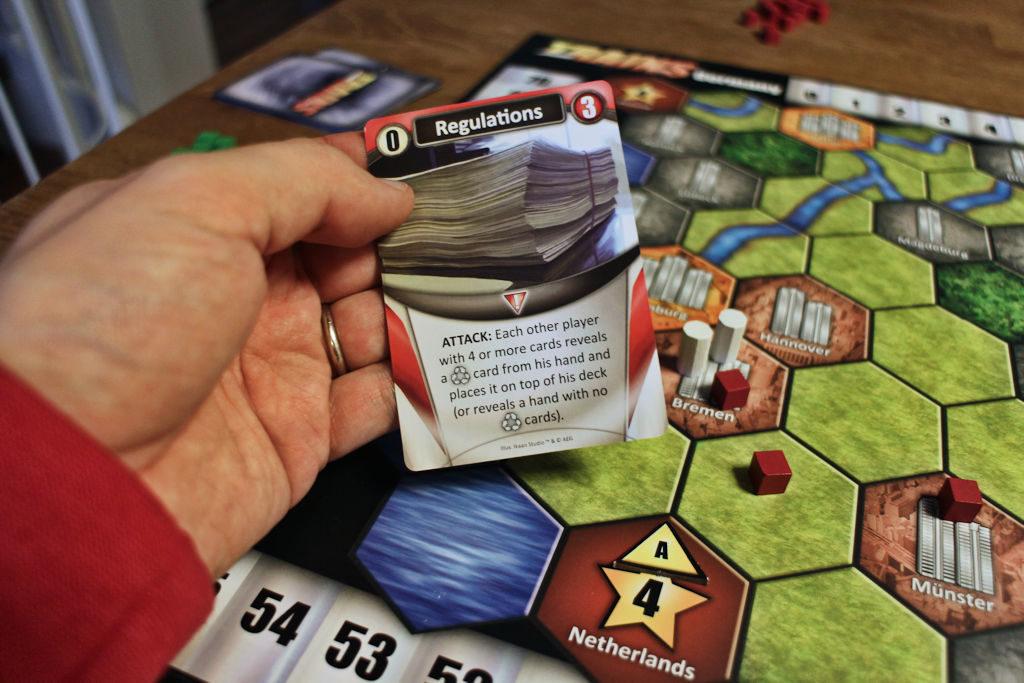 Esimerkki Trains: Rising Sunin kiusakortista: muiden pelaajien jätekortit kädessä aihettavat pientä lisäharmia.