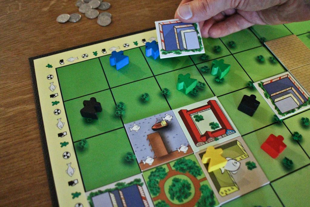 """Sininen pelaaja rakentamassa neutraalia rakennusta. Tämä laukaisee tien rakentumisen laudalle, sillä satamaan (sininen """"kalalaatta"""") pitää saada tie."""