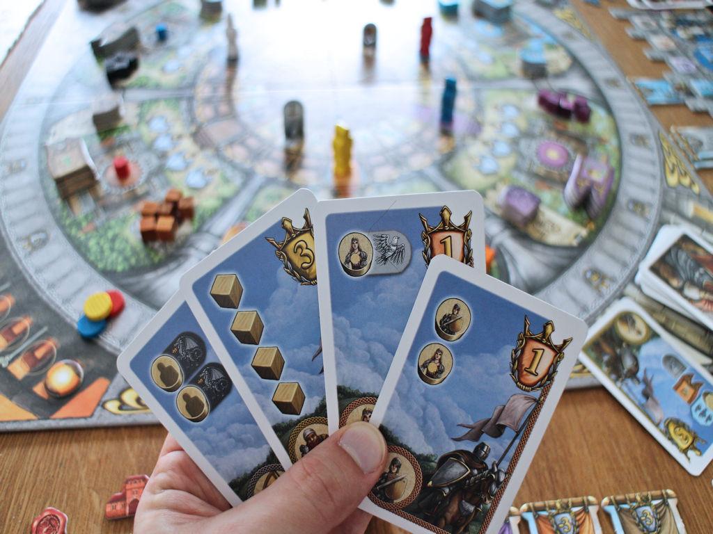 Tavoitekortteja: Päällimmäinen antaa pisteen, kun kaksi tiettyä työläistä saa samaan linnoitukseen. Seuraavassa tietty työläinen pitää saada tiettyyn linnoitukseen. Neljällä rakennuskuutiolla saa kolme pistettä jne.