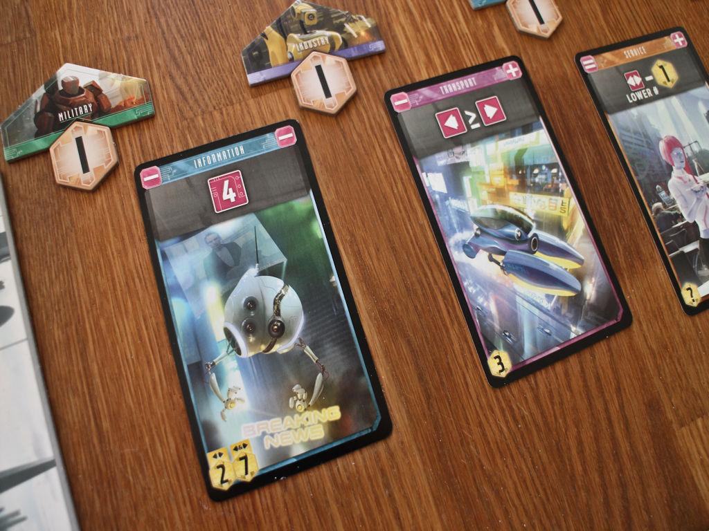 Lähikuvaa korteista: Vasemmalla oleva informaatiorobotti haluaa ympärilleen noppia, joiden silmäluku on 4. Kuljetusrobotti taas vasemmalle suuremman tai yhtäsuuren nopan kuin oikealle. Korttien alalaidassa tarjolla olevat pisteet korteista.