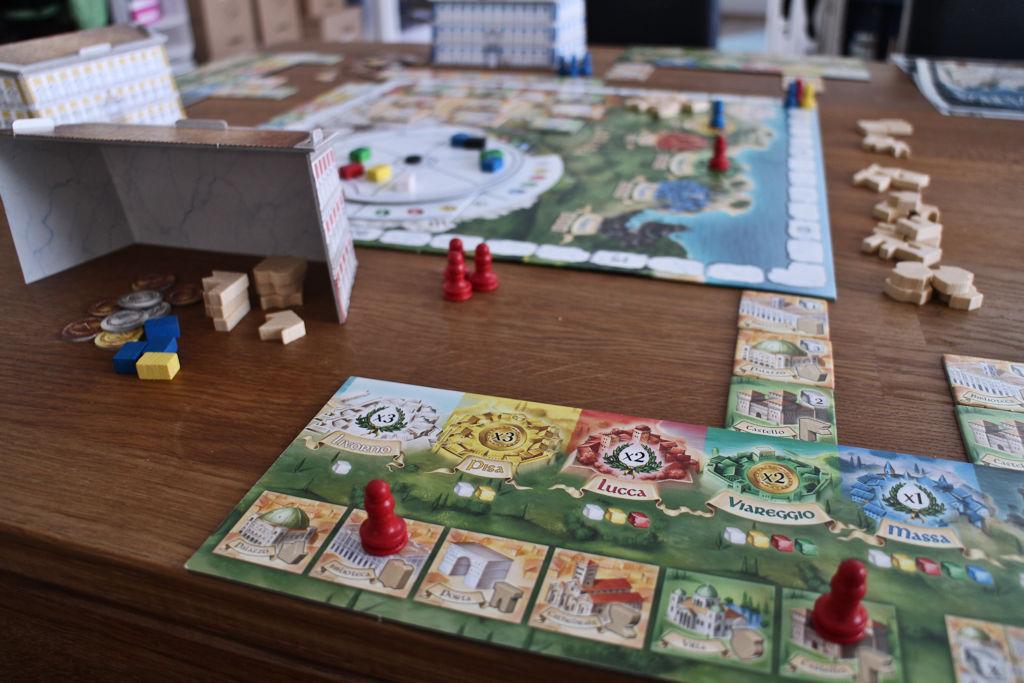 Punainen pelaaja on kaksi rakennustyyppiä jo pisteytettänyt, mistä merkkinä pisteytysnappulat vastaavien rakennusten kohdalla.